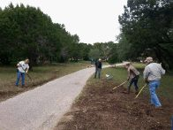 Volunteers rake up flood debris (click to enlarge)